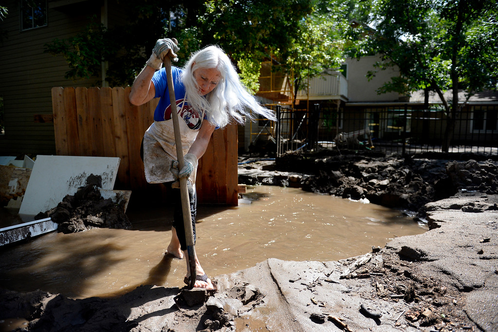 Description of . BOULDER, CO. - SEPTEMBER 17: Lol Smith works to divert water from the home of Kim Schuler on Upland Ave in Boulder, CO September 17, 2013. Schuler's property abuts Four Mile Creek and the home was flooded through out week. Colorado officials on Monday updated the number of people killed in the state's floods to as many as eight, as rescue helicopters took to the skies and emergency operations continued. Flooding in 15 Colorado counties has destroyed 1,502 homes and damaged 17,494 leaving more than 11,000 people evacuated, according to the Colorado Office of Emergency Management. (Photo By Craig F. Walker / The Denver Post)
