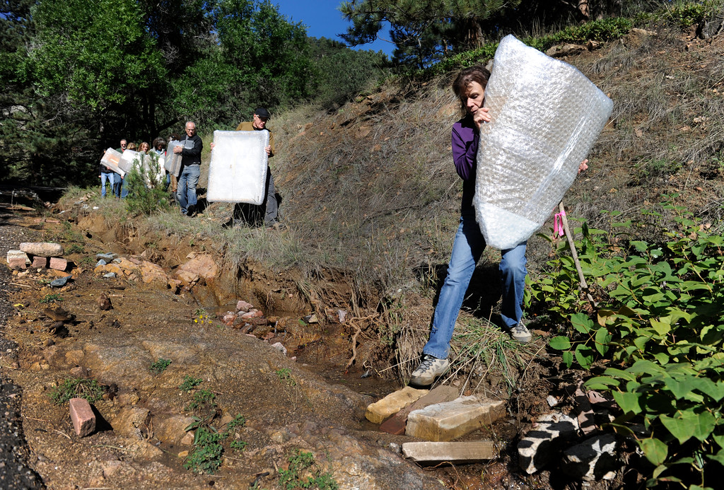 Description of . BOULDER, CO - Sept. 28: With Ellen Greenhouse leading the way, the group carefully crosses a culvert using two stones as a bridge. Friends and fellow Boulder artists gather to hike in to the home and studio of artist Marco Montanari to rescue and carry out his Encaustic paintings that need to be packed and sent to New York for a show in November. Montanari's home and studio did not suffer damage in the floods, but all roads leading in and out had been impassable up until just a few days ago. The group was able to drive a short distance up Wagon Wheel Gap Road and hiked the rest of the way in and out. (Photo By Kathryn Scott Osler/The Denver Post)