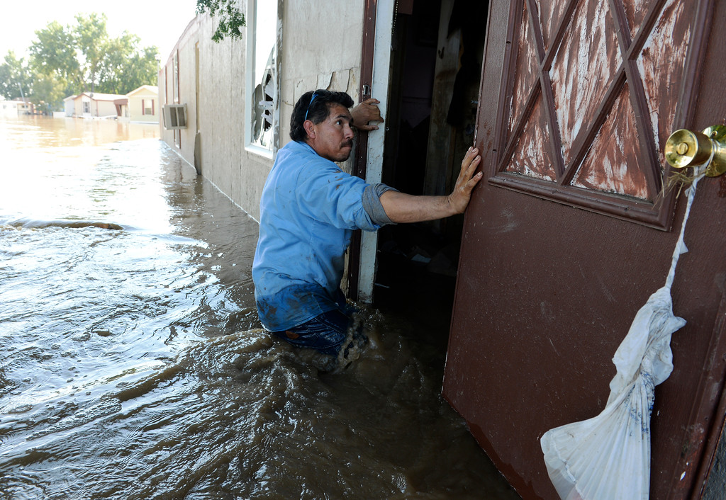 Description of . EVANS, CO - SEPTEMBER 16: Evans Resident Rito Romero heads back to his home to carry out belongings from his families flooded home, September 16, 2013. Massive flooding continues to hit Colorado. (Photo By RJ Sangosti/The Denver Post)