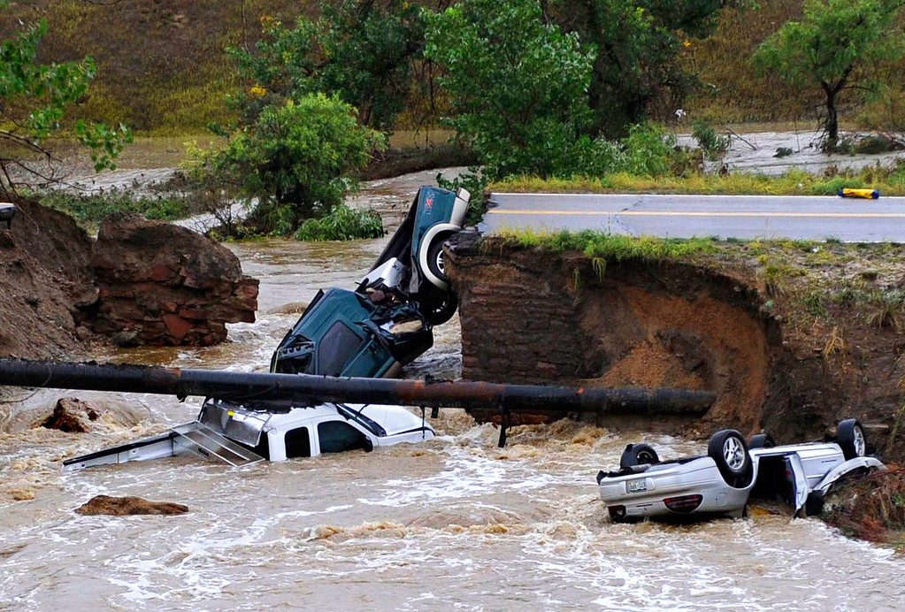 Description of . Three vehicles lie in a creek after raging floodwater undercut Dillon Road near U.S. 287 in Broomfield, Colo. on Sept. 12, 2013. The three motorists were rescued from the vehicles after emergency workers secured the vehicles with ropes and the motorists scrambled up the banks of the creek.