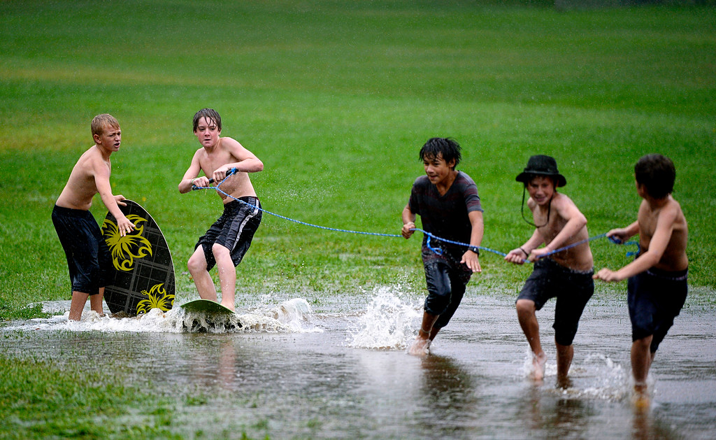 Description of . BOULDER, CO. - SEPTEMBER12:  A group of kids use a flooded field for skim-boarding at North Boulder Park in Boulder, Colo. on September 12, 2013. Record-breaking rain turned normally quiet creeks into raging, brown torrents that swept through Boulder, flooding homes, swamping cars and closing roads and schools. (Photo By Craig F. Walker / The Denver Post)