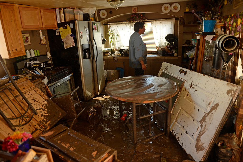 Description of . EVANS, CO - SEPTEMBER 16: Evans Resident Rito Romero checks out the damage in his families flooded home, September 16, 2013. Massive flooding continues to hit Colorado. (Photo By RJ Sangosti/The Denver Post)