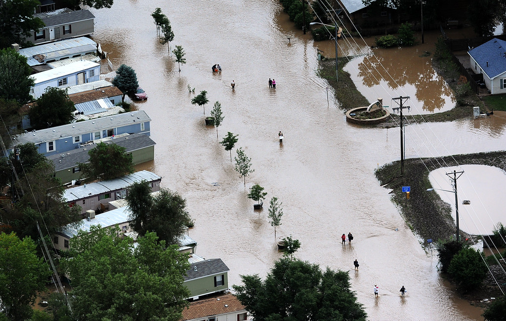 Description of . EVANS, CO. - SEPTEMBER 16:  People walk down 37th street in Evans, Colorado, carrying belongings recovered from flooded  homes in the area. Aerial photographs of the Platte River flooding cities and farms in Weld County Colorado. (Photo By Tim Rasmussen/The Denver Post)