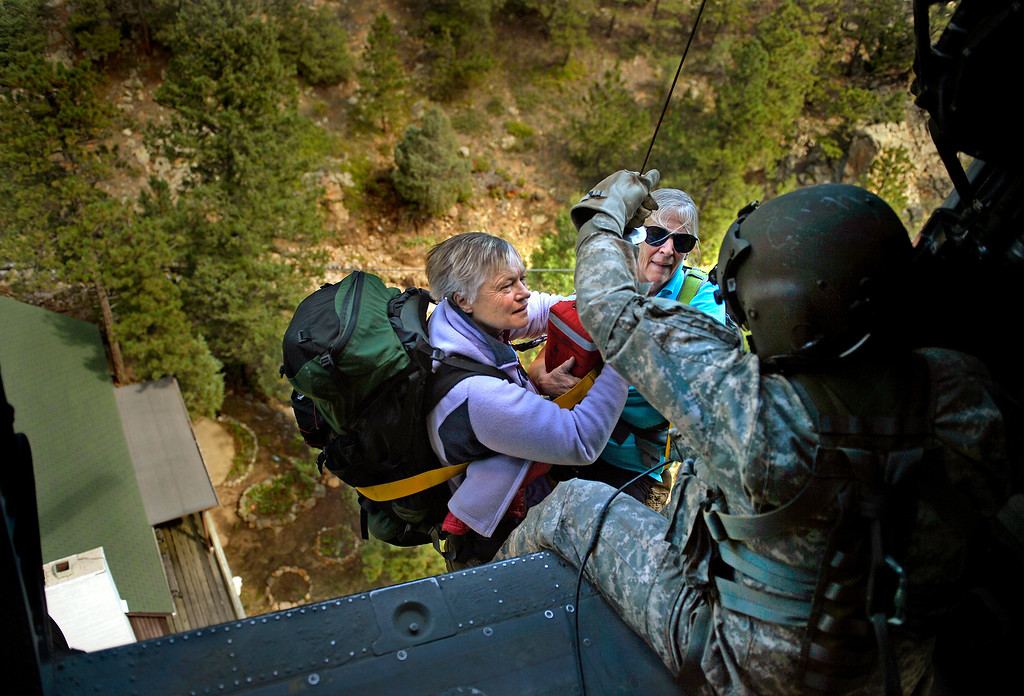 Description of . Sgt. 1st Class Keith Bart, based in Fort Carson, hoists two women aboard a UH-60 Black Hawk during a rescue near Jamestown on Sept. 17, 2013. Bart noticed the women as they waved red scarves from the deck of a home. State officials estimated about 600 people were still stranded in isolated areas.