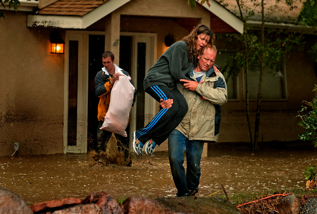 Description of . Kim Schuler carries his wife, Cheryl, across water and mud Sept. 12, 2013. Son Kyle also exits the Boulder home with some of the belongings they could salvage. The first floor of the home was flooded with 4 feet of water. More heavy rain was expected that night, as the state braced for the worst flooding in its history.