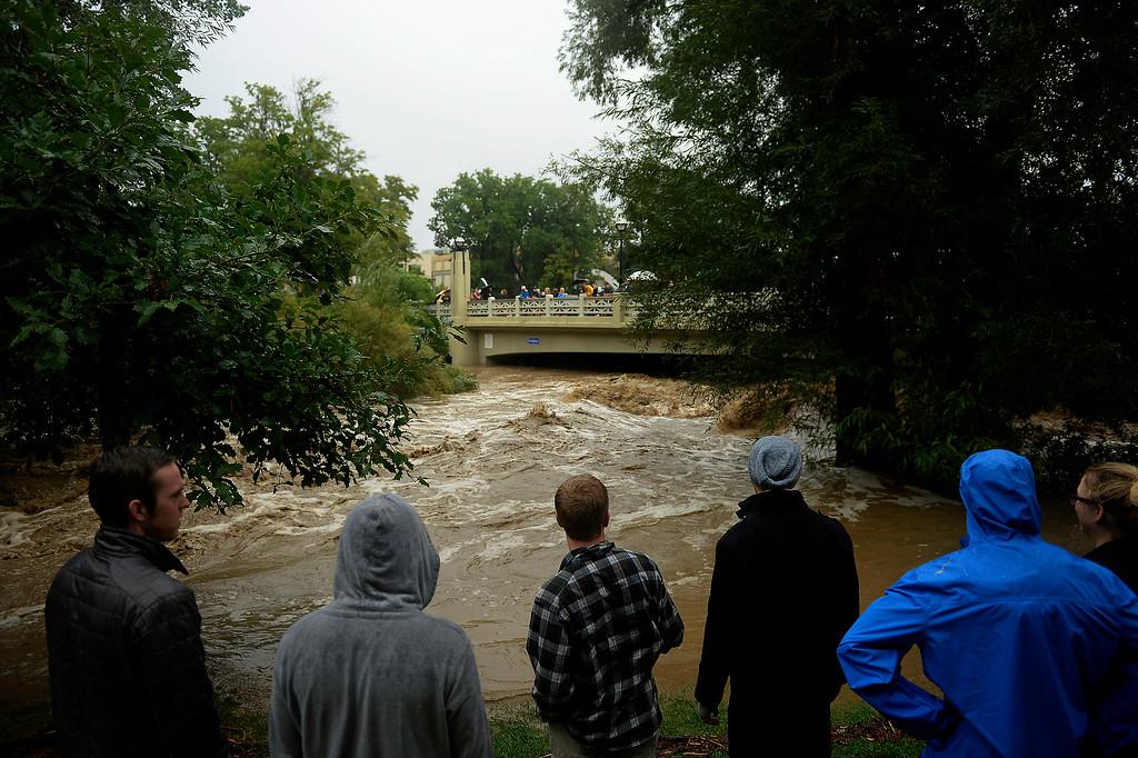 Description of . BOULDER, CO. - September 12: People watch the high water in Boulder Creek after heavy rains caused flash flooding and damage in Boulder, September 12, 2013 in Boulder, Colorado. (Photo By Joe Amon/The Denver Post)