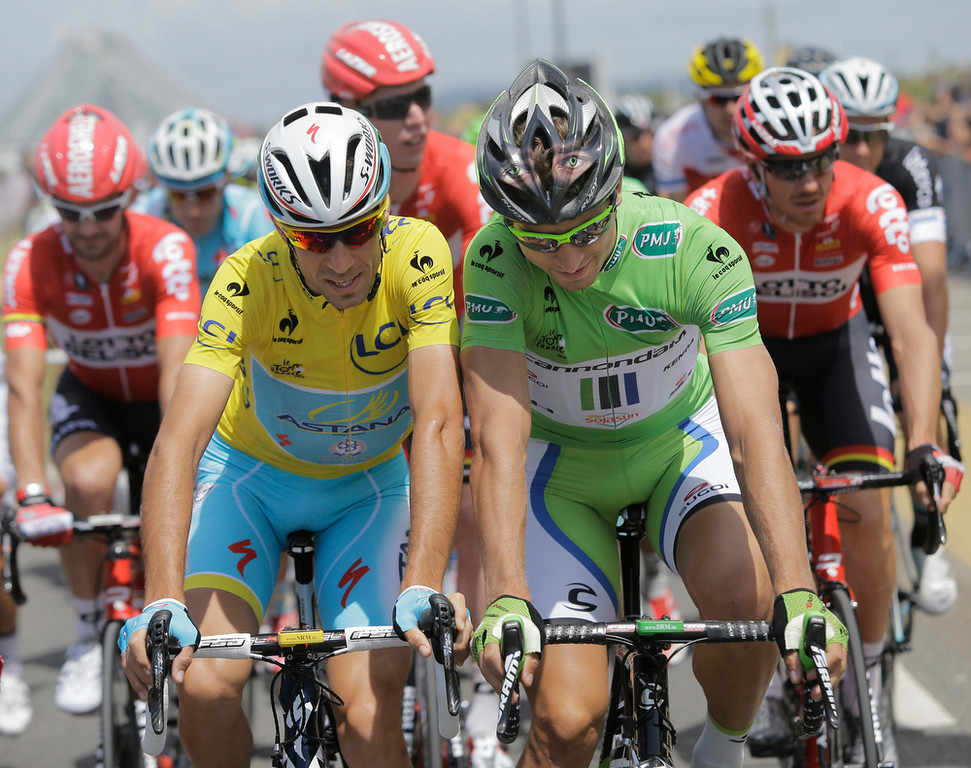 Description of . Italy's Vincenzo Nibali, wearing the overall leader's yellow jersey, and Peter Sagan of Slovakia, wearing the best sprinter's green jersey, ride shoulder-to-shoulder during the ceremonial procession prior to the start of the fourth stage of the Tour de France cycling race over 163.5 kilometers (101.6 miles) with start in Le Touquet and finish in Lille, France, Tuesday, July 8, 2014. (AP Photo/Laurent Cipriani)