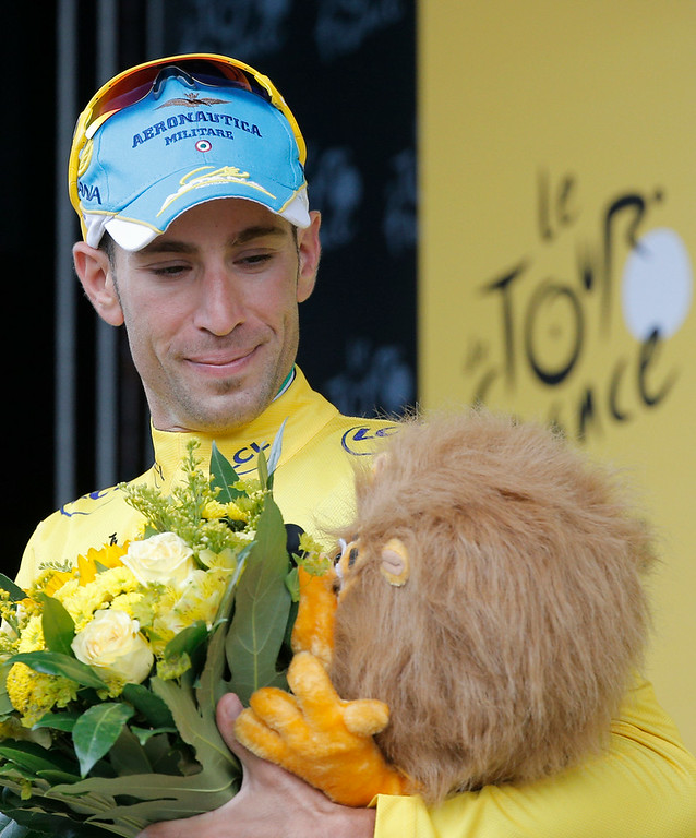 Description of . Italy's Vincenzo Nibali, wearing the overall leader's yellow jersey,  looks at the trophy as he celebrates on the podium of the fourth stage of the Tour de France cycling race over 163.5 kilometers (101.6 miles) with start in Le Touquet and finish in Lille, France, Tuesday, July 8, 2014. (AP Photo/Christophe Ena)