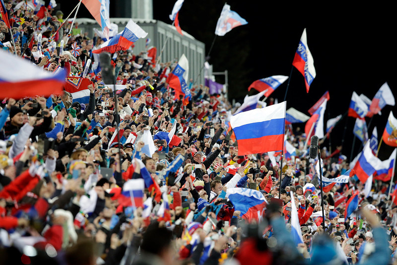 Description of . Fans wave flags as they celebrate after Russia won the men's biathlon 4x7.5K relay at the 2014 Winter Olympics, Saturday, Feb. 22, 2014, in Krasnaya Polyana, Russia. (AP Photo/Lee Jin-man)