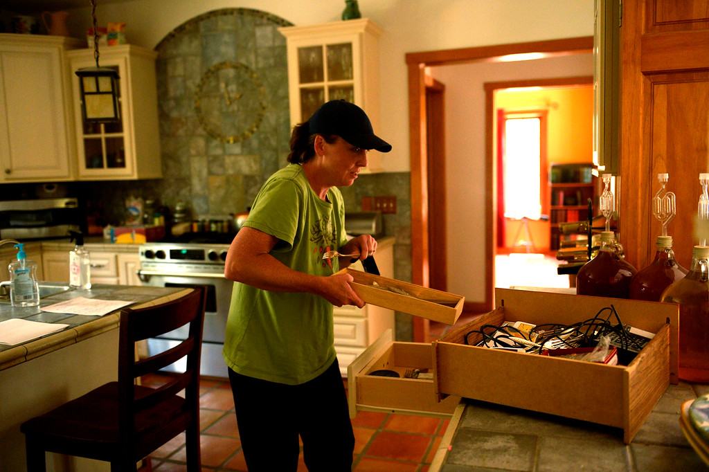 Description of . COLORADO SPRINGS, CO. - June 14: Deanna Martin fills a drawer with the families account info and passwords and videos of her 2 children\'s childhood in the home she and her husband Troy built as some residents were allowed back into the Black Forest Fire area to quickly get medications and important items that were left behind in the rush to evacuate near Colorado Springs, Colorado. June 14, 2013 Denver, Colorado Springs. (Photo By Joe Amon/The Denver Post)