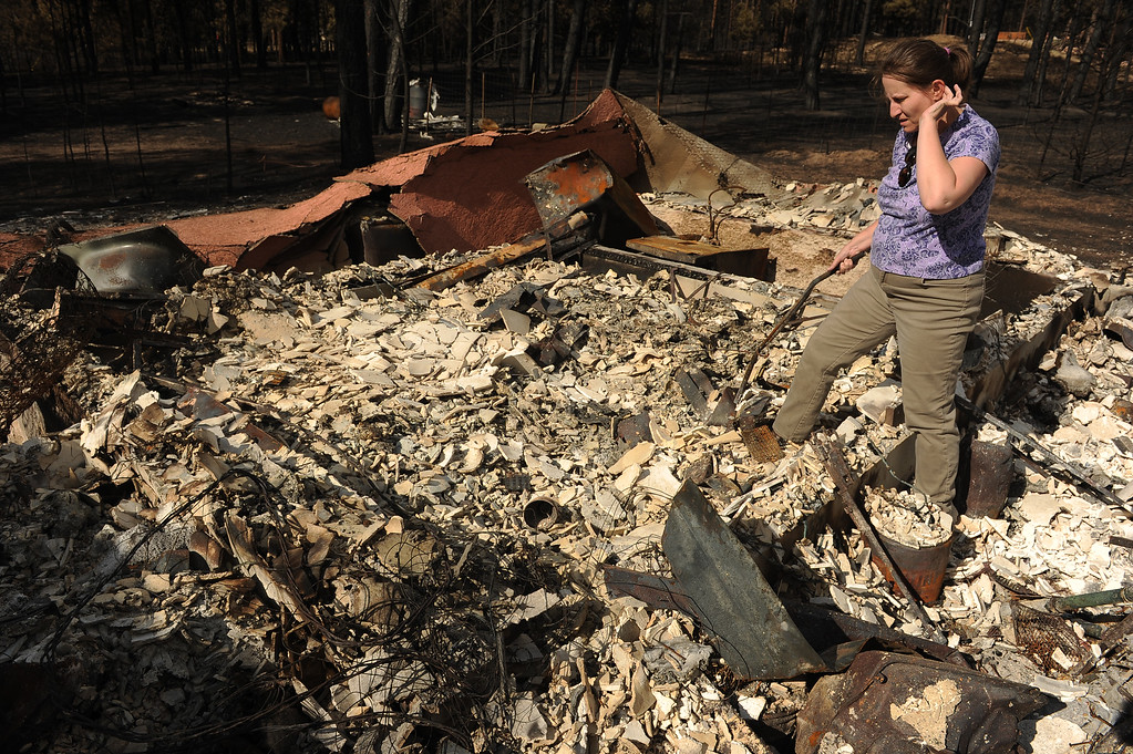 Description of . BLACK FOREST, CO - JUNE 18:  Amy Feik sifts through the rubble of what was the home she shared with boyfriend Robert Runyard in Black Forest, Co on June 18, 2013.  Feik and Robert Runyard, not pictured, returned home for the first time to their home on Swan Road in Black Forest, CO on June 17, 2013.  Residents of Black Forest were finally allowed back into their burned homes for the first time since the fire devoured thousands of acres inside the Black Forest taking with it 502 homes and two lives.  Photo by Helen H. Richardson/The Denver Post)
