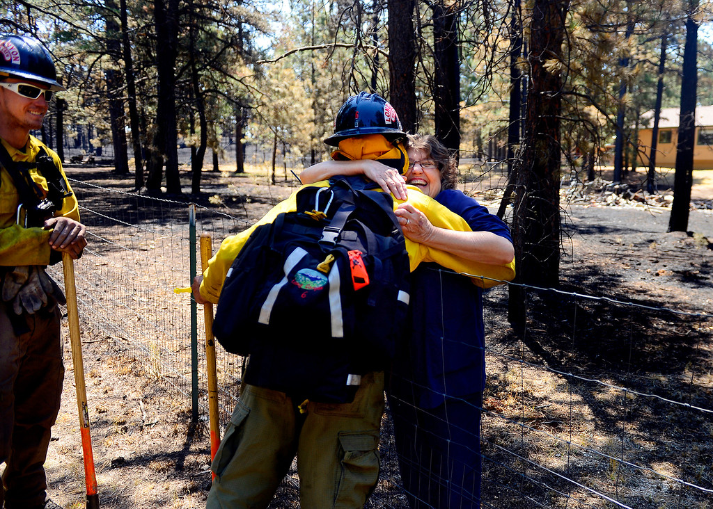 Description of . Long Canyon Wildland firefighter Lynn Reynolds is hugged by homeowner Jody Wallace as he and his crew look for hot spots at a burned property on Pine Glen Drive. Only one home on the loop of Pine Glen Drive burned in the fire, and Wallace wanted to personally thank the firefighters for saving her adjacent home.