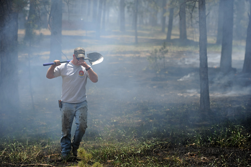 Description of . COLORADO SPRINGS, CO - JUNE 12:  Matt Newland takes a break from helping put out small fires with friend Chad Mazari around neighbors houses off of Cyprus road in the Black Forest on June 12, 2013. He and his friend Matt Newland stayed close to their house on Herring Road to make sure they could watch the fire to protect their house.  They had all of their belongings ready to go and an escape route in place in case they need to leave. So far the fire has moved east of their house, but the Black Forest fire continues to burn and has yet to have any containment.   Photo by Helen H. Richardson/The Denver Post)