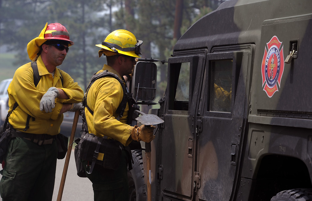 Description of . Sgt. Ryan Hawley, right and Specialist Chris Butterfield, left, talk with crew members to decide their next move near Winchester Road north of Hodgen Road in the midst of the Black Forest Fire on June 13, 2013.  They are with the National Guard out of Fort Carson.  Photo by Helen H. Richardson/The Denver Post)
