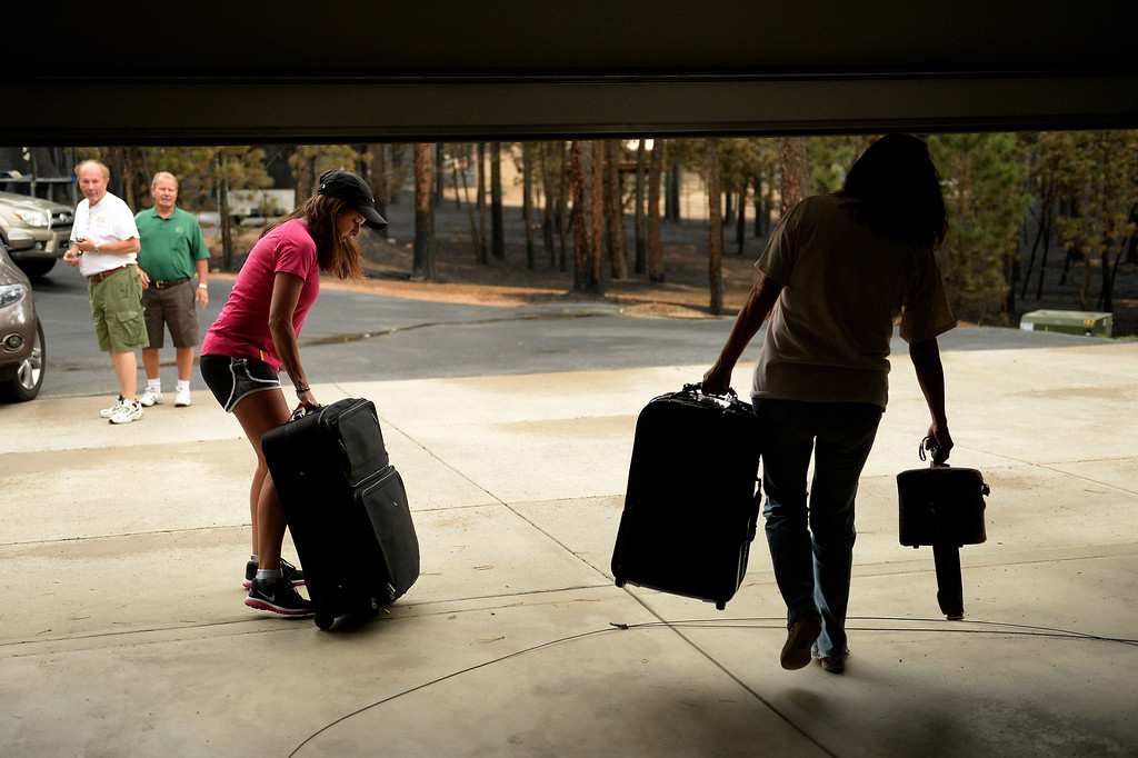 Description of . COLORADO SPRINGS, CO. - June 14: Alicia Taylor and her mother Lana Forey hurry from their house with their bags as some residents were allowed back into the Black Forest Fire area to quickly get medications and important items that were left behind in the rush to evacuate near Colorado Springs, Colorado. June 14, 2013 Denver, Colorado Springs. (Photo By Joe Amon/The Denver Post)