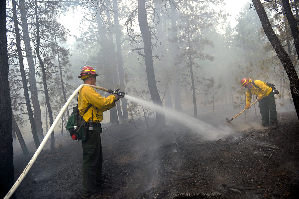 Description of . st Sgt John Screiber, left, helps puts water on hotspots while Sgt David Meggison, left uses his tool to do the same thing puts   on property along Winchester Road north of Hodgen Road in the midst of the Black Forest Fire on June 13, 2013. Photo by Helen H. Richardson/The Denver Post)
