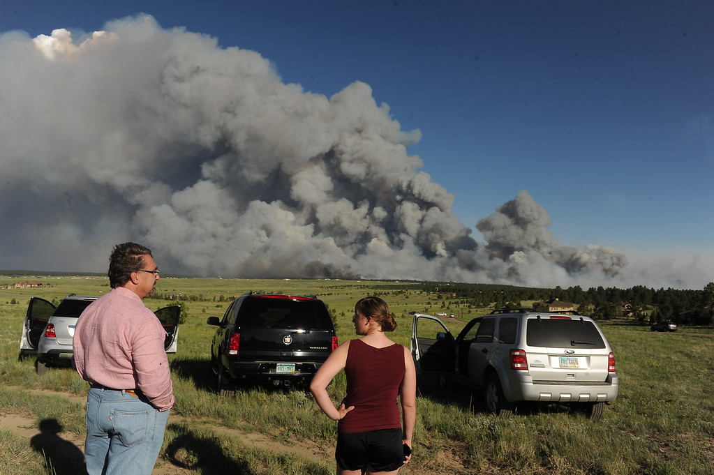 Description of . COLORADO SPRINGS, CO - JUNE 11: Homeowners watch the fire from a high meadow north of the fire. A wild land fire started around 2:00 in the Black Forest northeast of Colorado Springs, CO on June 11, 2013.  Homes have already burned and the wind is expected to continue through the afternoon.  Photo by Helen H. Richardson/The Denver Post)