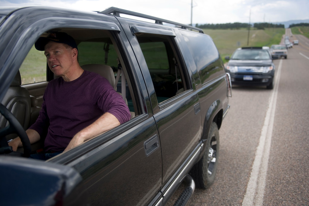 Description of . Dan Bartlett waits in line at Highway 83 and Hodgen Road to be escorted to his home in Black Forest by police on Saturday, June 15, 2013. Police were only letting residents in with proof of residence for pets or medications. Cars in the front of the line had been waiting for upwards of three hours for their escort.(Photo By Grant Hindsley / The Denver Post)