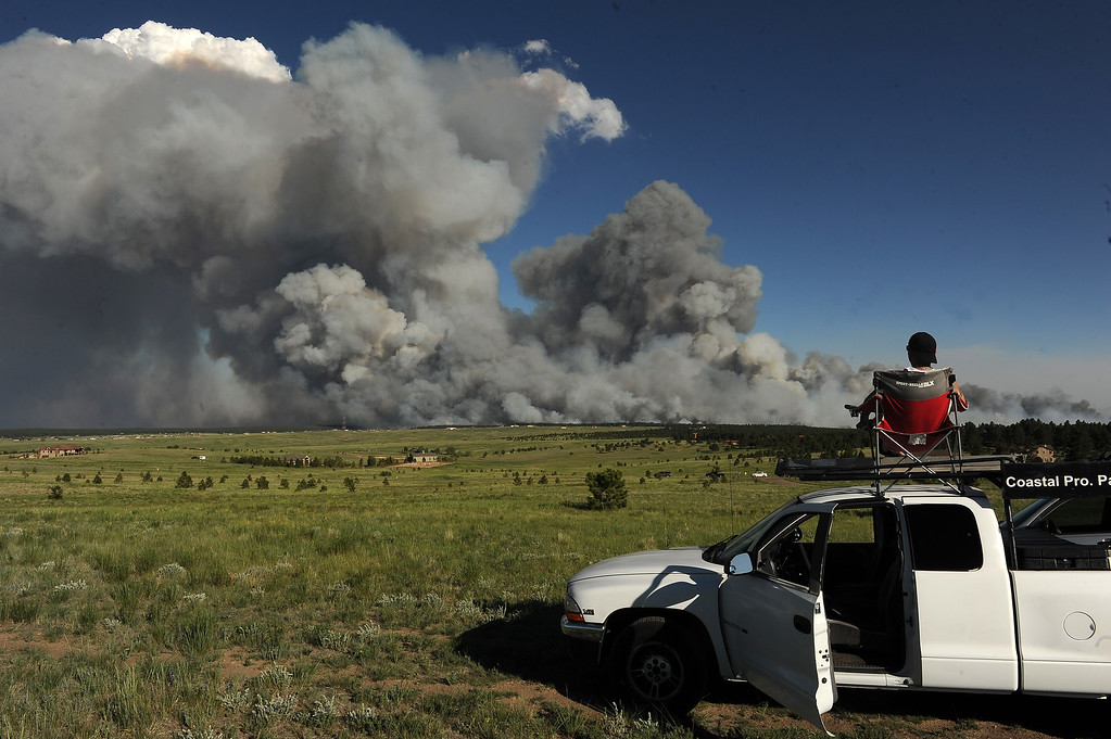 Description of . COLORADO SPRINGS, CO - JUNE 11: Shaun Buhrman, of Aurora, watches the fire from a high meadow north of the fire. A wild land fire started around 2:00 in the Black Forest northeast of Colorado Springs, CO on June 11, 2013.  Homes have already burned and the wind is expected to continue through the afternoon.  Photo by Helen H. Richardson/The Denver Post)