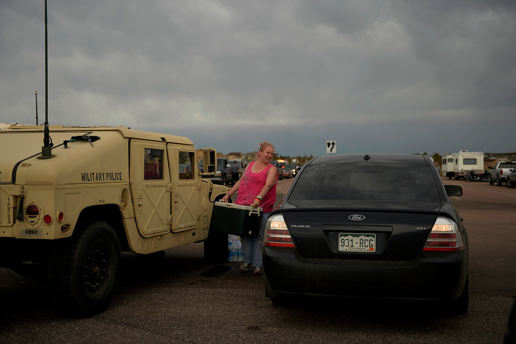 "Description of . COLORADO SPRINGS, CO. - June 14: Nicolette Dimaggo grabs her cooler after her escort into the Black Forest Fire area to quickly get medications and important items that were left behind in the rush to evacuate near Colorado Springs, Colorado. Nicolette drove for over four hours delivering drinks and snacks to all of the National Guardsmen, firefighters and police she could find, They saved my home,"" she said.  June 14, 2013 Denver, Colorado Springs. (Photo By Joe Amon/The Denver Post)"