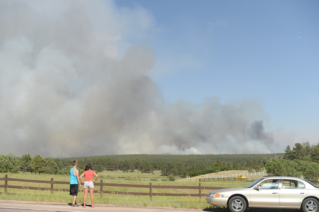 Description of . Colorado Springs, CO. - June 11: Annie Kostenbauer, 19, right, and Dustin Wilkins, 19, of Monument are watching the smoke covered Black Forest area. Colorado Springs, Colorado. June 11, 2013. The fire is about 15 acres near the 12600 block of Peregrine Way near Black Forest Regional Park. (Photo By Hyoung Chang/The Denver Post)