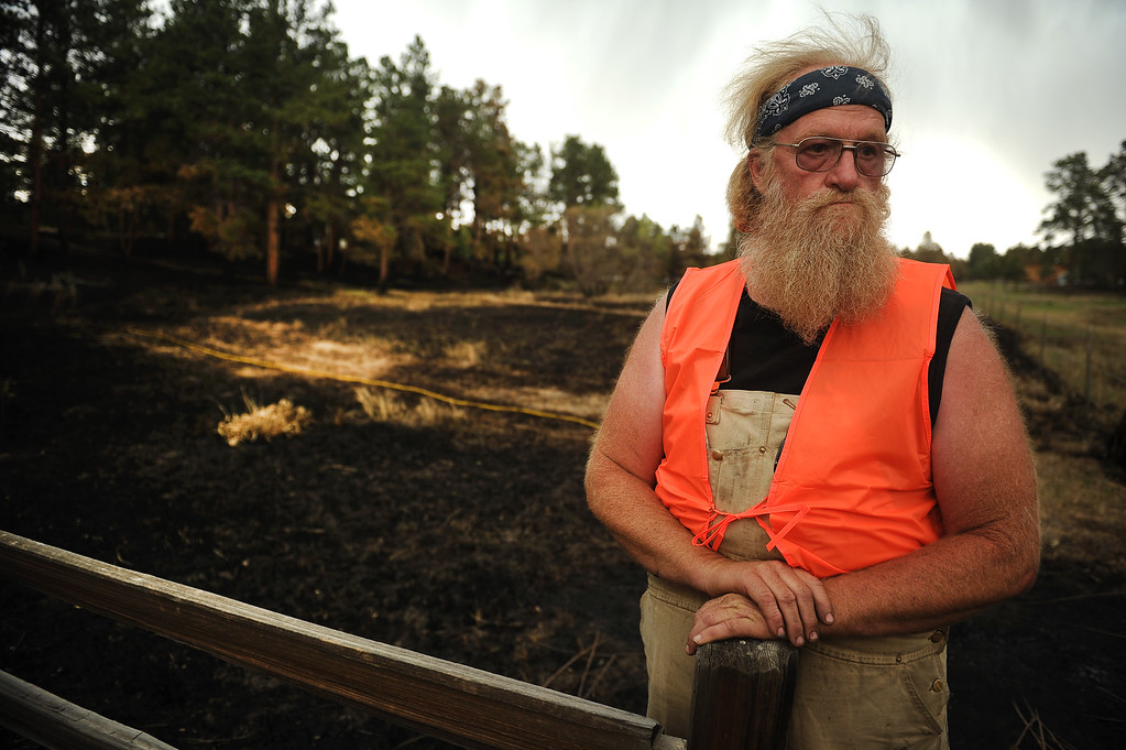 Description of . BLACK FOREST, CO - JUNE 17:   Mike Turner is seen along the fence line of his mother\'s property along Shoup Road inside the Black Forest Burn area on June 17, 2013.  His mother, who is 90 years old, has lived in the Black Forest for 49 years.  She lost everything in the fire.  This is her property that Turner is standing on. Turner never evacuated and stayed with a friend across the street and tried to save what he could during the firestorm.  Photo by Helen H. Richardson/The Denver Post)