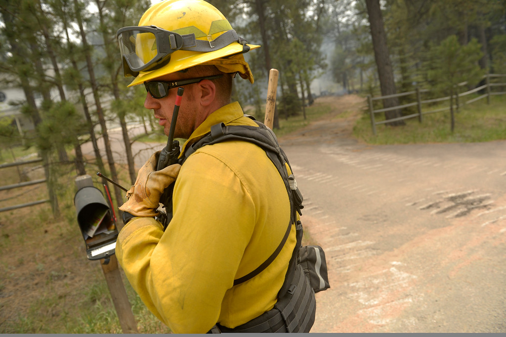 Description of . Ryan Hawley, with the National Guard out of Fort Carson, directs his firefighters to a house to help put out small fires in and around structures near Winchester Road north of  Hodgen Road in the midst of the Black Forest Fire on June 13, 2013.  Photo by Helen H. Richardson/The Denver Post)