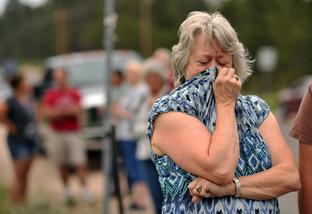 Description of . Black Forest Fire evacuee Karen Hilborn covers her face from smoke during her waiting El Paso County Sheriff\'s escort to their property at the corner of Vollmer Rd. and Burgess Rd., June 14, 2013. Firefighters continue to battle the Black Forest fire north of Colorado Springs that has consumed 15,700 acres and 379 homes. (Photo By Hyoung Chang/The Denver Post)