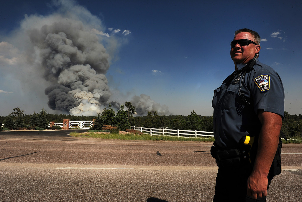 Description of . COLORADO SPRINGS, CO - JUNE 11: Colorado Springs patrolman Herb Tomitsch watches as a huge plume of smoke continues to grow along Highway 83 near Colorado Springs, CO on June 11, 2013.  A wild land fire started around 2:00 in the Black Forest northeast of Colorado Springs, CO on June 11, 2013.  Homes have already burned and the wind is expected to continue through the afternoon.  Photo by Helen H. Richardson/The Denver Post)