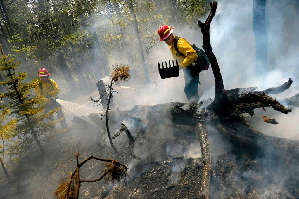 Description of . Sgt. 1st Class John Screiber, right, and Sgt. David Meggison extinguish a burning tree on property along Winchester Road north of Hodgen Road in the middle of the Black Forest fire on June 13, 2013. They are members of a firefighting crew with the National Guard from Fort Carson. The crew used a water tender that carries 2,500 gallons of water to fight fire in an area that has no fire hydrants.