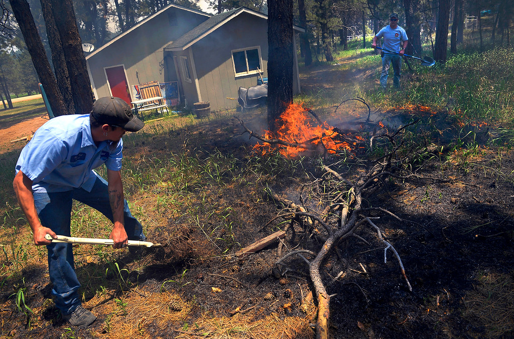 Description of . Matt Newland, left, and his friend Chad Mazari use shovels to put out small spot fires near a neighbor\'s home off Cyprus Road in the Black Forest on June 12, 2013. Both men, who ignored evacuation orders, had packed their belongings and had an escape route in mind in case they needed to leave quickly.