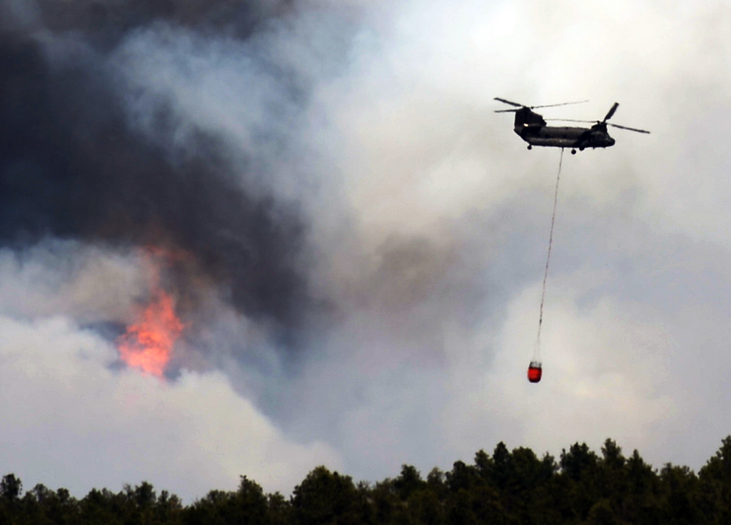 Description of . COLORADO SPRINGS, CO. - June 12: A helicopter is heading to the fire site. Colorado Springs, Colorado. June 12, 2013. According to El Paso County Sheriff Terry Maketa, the Black Forest Fire north of Colorado Springs has already burned 80 to 100 homes. (Photo By Hyoung Chang/The Denver Post)