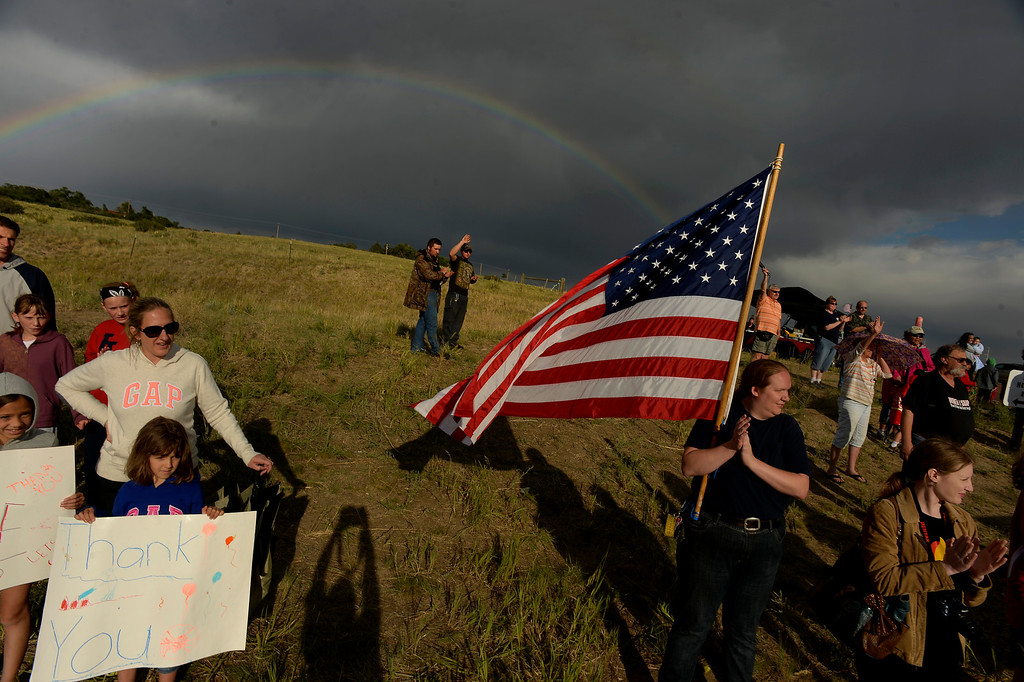 Description of . BLACK FOREST, CO - JUNE 17:   Cyrena McVey holds up a large American flag while a beautiful double rainbow sits over the Black Forest Fire burn area while Colorado Springs residents turn out each and every night with signs and flags to cheer on the firefighters as they come off the line for the night from fighting the Black Forest Fire in Black Forest on June 17, 2013.  Photo by Helen H. Richardson/The Denver Post)