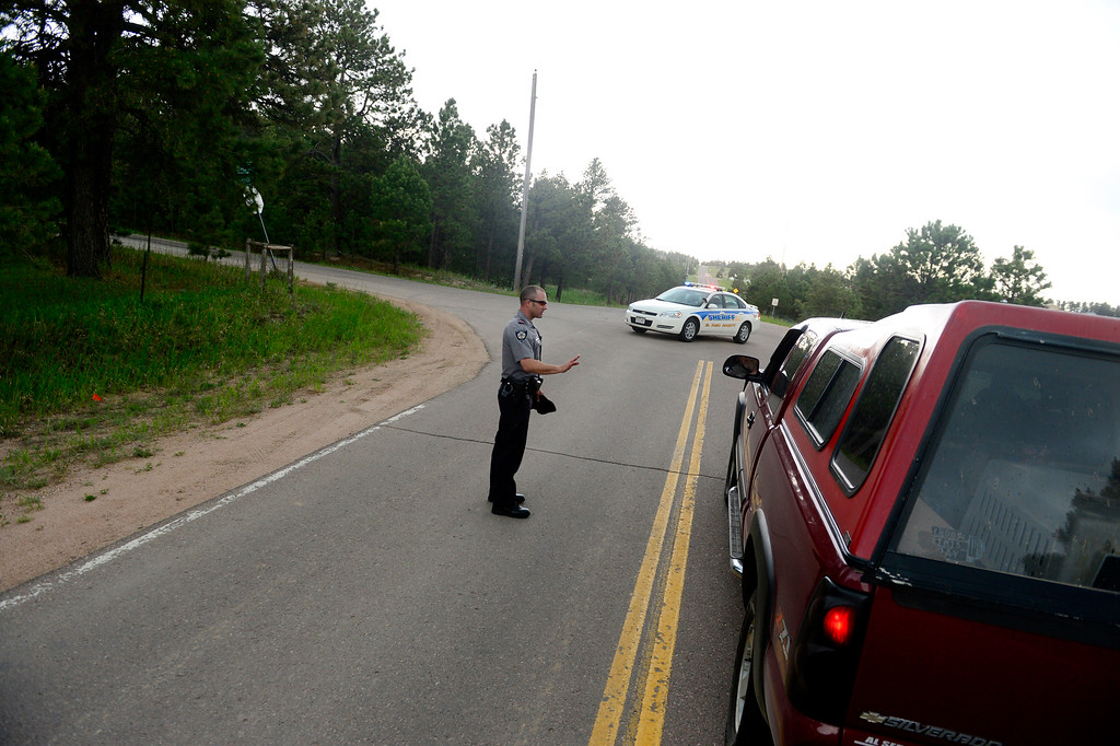 Description of . COLORADO SPRINGS, CO - JUNE 17: Andrew Thompson, of the El Paso County Sheriff\'s department, checks the IDs of residents before letting them cross a roadblock at the intersection of Wildridge and Herring Roads. As of Sunday, some select area evacuated Black Forest fire residents were allowed to return to their homes. (Photo by AAron Ontiveroz/The Denver Post)
