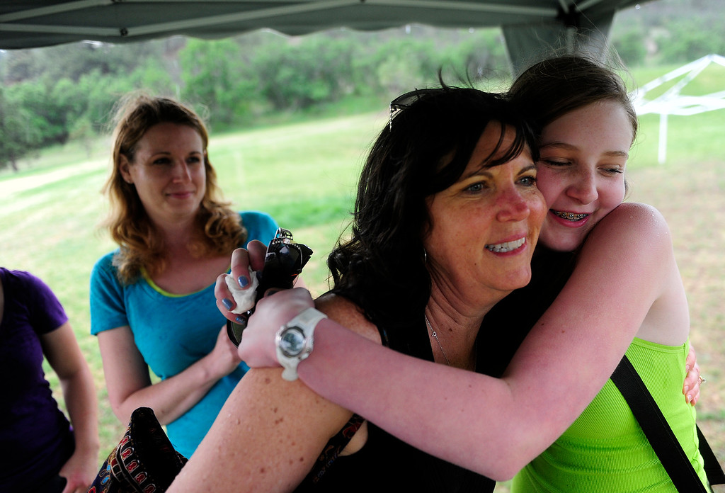 Description of . COLORADO SPRINGS - JUNE 17: Caitlyn DelMonico, right, hugs Suzanne Lung, as her mother Delcine DelMonico watches, at the end of a picnic Waldo Canyon evacuees and community members put on to support those affected by the Black Forest Fire on Monday, June 17, 2013. Lung and Wendy Reis, not pictured, got the idea to put on the picnic after seeing the DelMonico\'s on TV after they lost their home.(Photo By Grant Hindsley / The Denver Post)