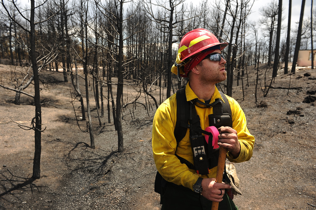 Description of . BLACK FOREST, CO - JUNE 17:   Aaron Cariato, a firefighter with Salida Fire and Rescue, checks for any kind of hotspots in houses inside the Black Forest fire zone on June 16, 2013. Officials want to make sure that all hotspots are out completely.  The crew also looks above in the burned canopy of trees looking for any limbs or trees that might fall over that might injure someone.  The fire is now 75% contained and recent rains are helping firefighters. Photo by Helen H. Richardson/The Denver Post)