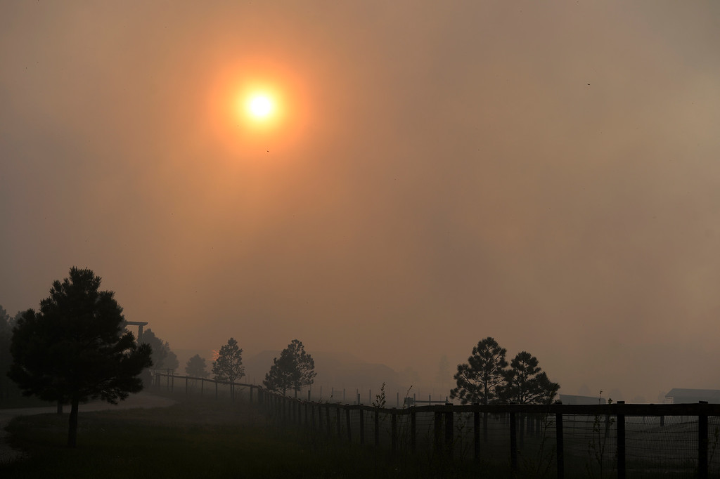 Description of . COLORADO SPRINGS, CO - JUNE 11: Smoke filled sky obscures the sun as the Black Forest Fire advances towards Herring Road in the Black Forest northeast of Colorado Springs, CO on June 11, 2013. Many homes have already been lost to the raging fire that continues to burn out of control. Photo by Helen H. Richardson/The Denver Post)