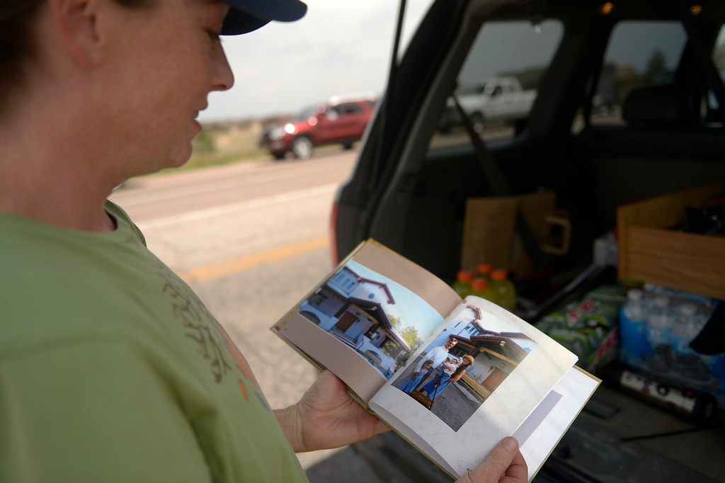 Description of . COLORADO SPRINGS, CO. - June 14: Deanna Martin looks at a small photo book she grabbed on her way out of her home after getting medications and the families account info and passwords and videos of her 2 children\'s childhood in the home she and her husband Troy built as some residents were allowed back into the Black Forest Fire area to quickly get medications and important items that were left behind in the rush to evacuate near Colorado Springs, Colorado. June 14, 2013 Denver, Colorado Springs. (Photo By Joe Amon/The Denver Post)