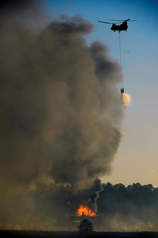 Description of . COLORADO SPRINGS, CO - JUNE 11: A Blackhawk helicopter makes a water drop on a burning structure in the midst of the Black Forest Fire in Colorado Springs, CO on June 11, 2013.. Many homes have already been lost to the raging fire that continues to burn out of control. Photo by Helen H. Richardson/The Denver Post)