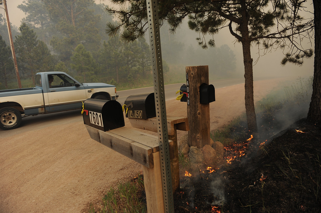 Description of . COLORADO SPRINGS, CO - JUNE 11: A man braves the smoke and heads into the fire in his pick up truck on Herring Road in the midst of the Black Forest Fire in Colorado Springs, CO on June 11, 2013.. Many homes have already been lost to the raging fire that continues to burn out of control. Photo by Helen H. Richardson/The Denver Post)