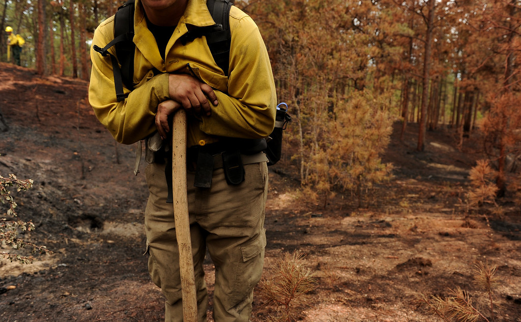 Description of . BLACK FOREST, CO - JUNE 17:   James Gonzales, with Wildfire Support Team from Santa Fe, New Mexico looks for any kind of hotspots on properties inside of the Black Fire fire zone in Black Forest, CO on June 17, 2013.  The fire is now 75% contained and recent rains are helping firefighters. Photo by Helen H. Richardson/The Denver Post)