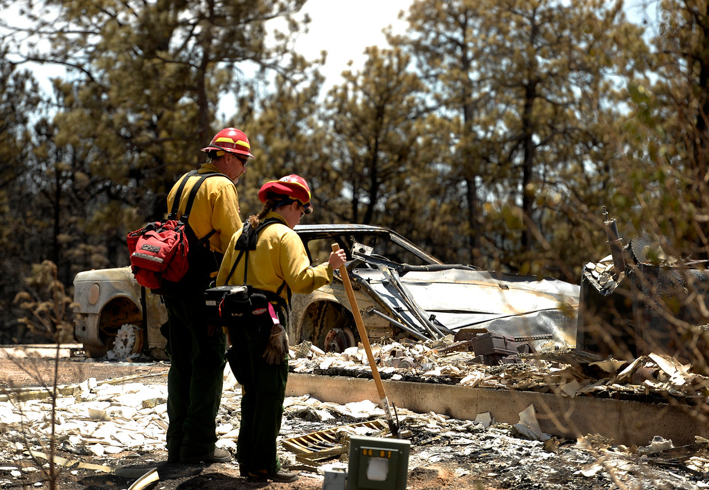 Description of . BLACK FOREST, CO - JUNE 17:   Salida Fire Department engine boss and captain David McCann, left, and firefighter Brandie Smith, look over burned homes in the Black Forest Fire sone on June 17, 2013.  The crew were checking for hotspots as well as marking  trees that they deem dangerous that might fall over  on burned properties.  They mark them and sawyers can come in later to cut them down.  The crew also looks above in the burned canopy of trees looking for any limbs or trees that might fall over that might injure someone.  The fire is now 75% contained and recent rains are helping firefighters. Photo by Helen H. Richardson/The Denver Post)