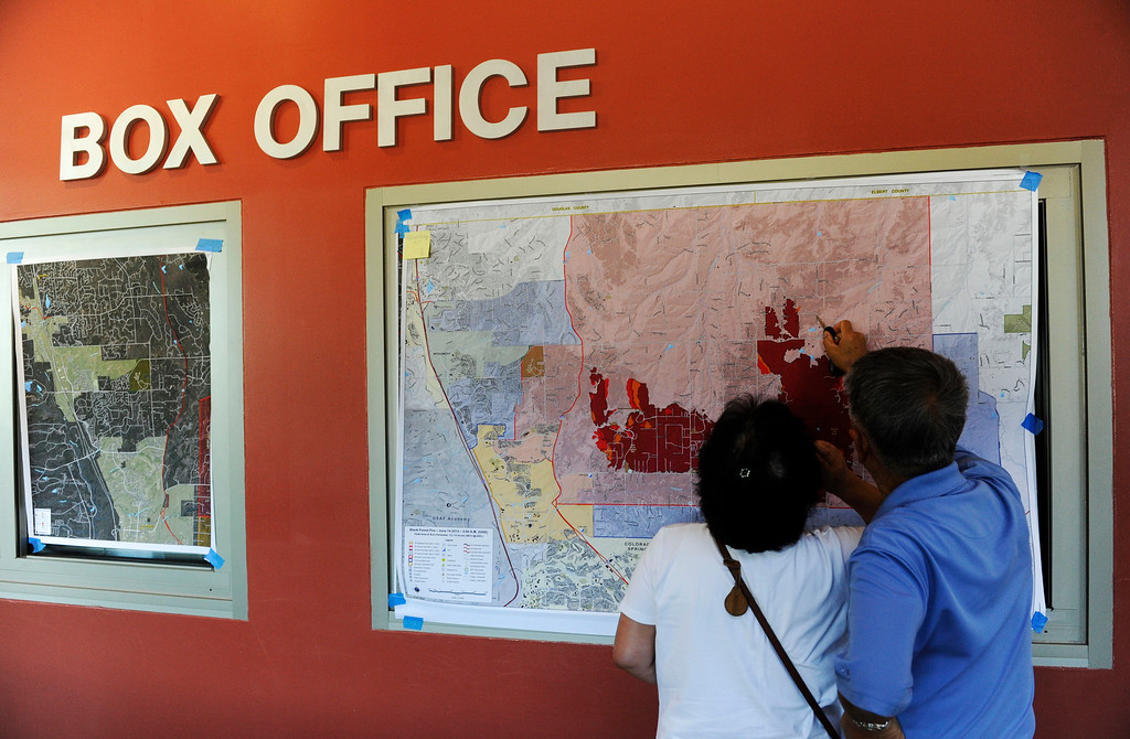 Description of . Myung Park and his wife, Kyeja Park, left, look over a burn area map of the Black Forest Fire trying to find out if their home has burned or not Saturday morning before a community meeting at Palmer Ridge High School in Monument Colorado June 15, 2013.  The couple later found out that their house did not burn.  (Photo By Andy Cross/The Denver Post)