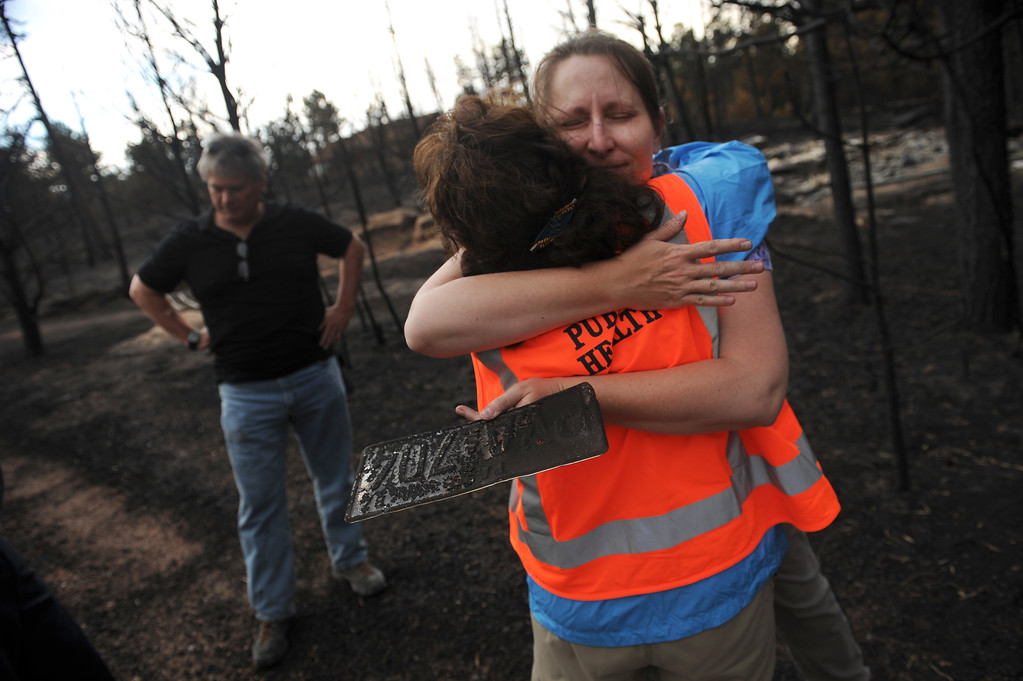 Description of . BLACK FOREST, CO - JUNE 17:  Homeowner Amy Feik, right, gets a hug from Monika Hannan, a public health psychologist with El Paso County on June 18, 2013 on the property she lived on with boyfriend Robert Runyard, left.  The couple returned home for the first time to their home on Swan Road in Black Forest, CO on June 17, 2013.  Residents of Black Forest were finally allowed back into their burned homes for the first time since the fire devoured thousands of acres inside the Black Forest taking with it 502 homes and two lives.  Photo by Helen H. Richardson/The Denver Post)