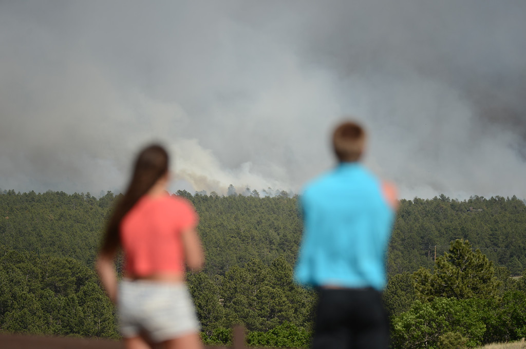 Description of . Colorado Springs, CO. - June 11: Annie Kostenbauer, 19, left, and Dustin Wilkins, 19, of Monument are watching the smoke covered Black Forest area. Colorado Springs, Colorado. June 11, 2013. The fire is about 15 acres near the 12600 block of Peregrine Way near Black Forest Regional Park. (Photo By Hyoung Chang/The Denver Post)