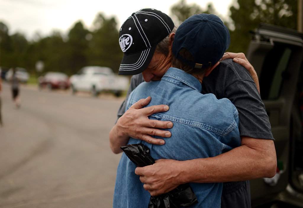 Description of . Black Forest Fire evacuees Cindy Miller, hugs her husband Ray before his going to their property with El Paso County Sheriff\'s escort at the corner of Vollmer Rd. and Burgess Rd, June 14, 2013. Ray went to pick up their truck. They lost their house by the fire. (Photo By Hyoung Chang/The Denver Post)