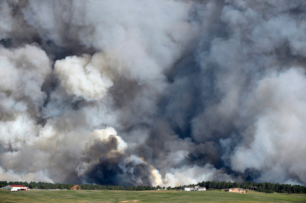 Description of . COLORADO SPRINGS, CO - JUNE 11: A wall of dark smoke looms large over the horizon as fire destroys the landscape looking south from Mountain Dance Drive and Open Sky Way northeast of Colorado Srpings, CO on June 11, 2013. The Black Forest fire started around 1:45 in an area of the Black Forest northeast of Colorado Springs, CO. Homes have already burned and the wind is expected to continue through the afternoon. Photo by Helen H. Richardson/The Denver Post)