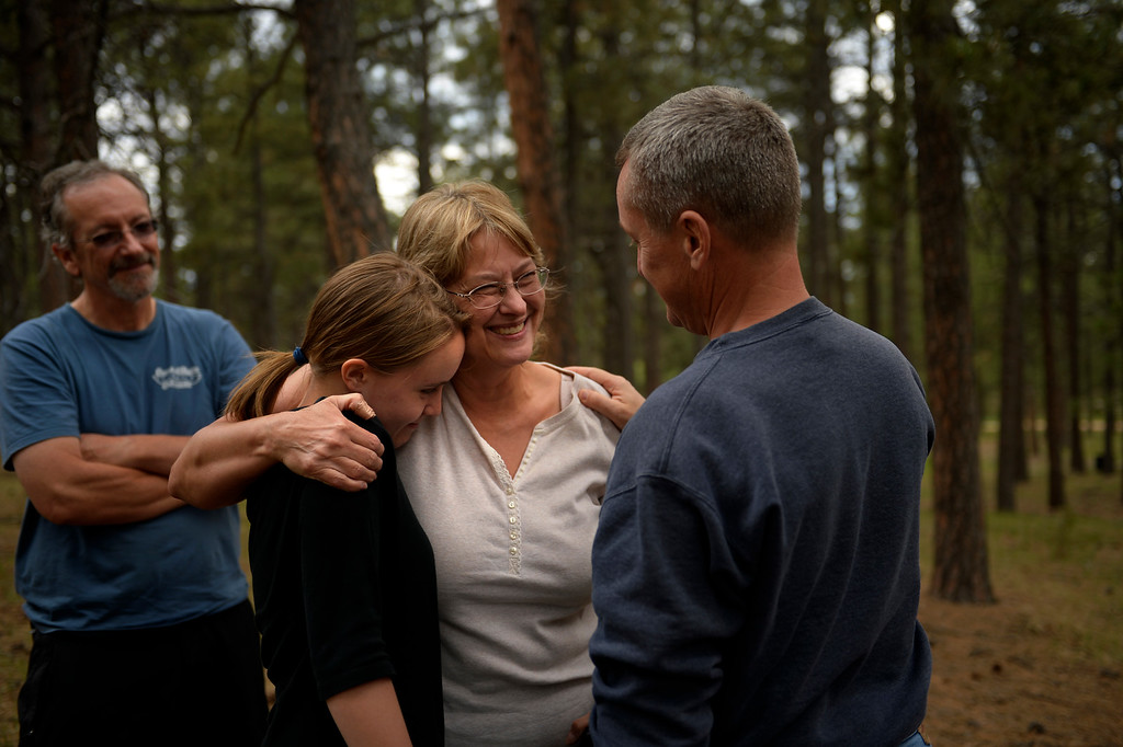 Description of . COLORADO SPRINGS, CO. - June 17: Nancy Trosper is hugged by 18 year old Lauren Haynes and her dad Hank while Paul Story watches from behind. The neighbors were thankful their houses were still standing as they walked with Nancy through her property this afternoon in Willow Springs Estates. Some residents were allowed back into the northern edge of the Black Forest Fire area near Colorado Springs, Colorado. June 17, 2013 Denver, Colorado Springs. (Photo By Joe Amon/The Denver Post)