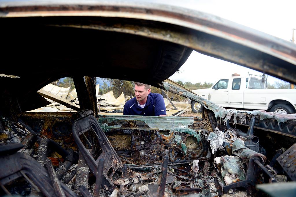 Description of . COLORADO SPRINGS, CO - JUNE 18: Jesse Russow surveys the damage of a Ford T-Bird on his rental property, which was the southernmost home burned on the west side of Vollmer Road. The occupant of the home, who was not named, was only able to save himself and his motorcycle as he was away from the property when the evacuation took place. Russow is accepting donations for fire crews at 7195 Templeton Gap Road in Colorado Springs. (Photo by AAron Ontiveroz/The Denver Post)