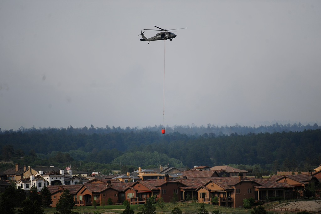 Description of . COLORADO SPRINGS - JUNE 13: A helicopter refills with water over Flying Horse in Colorado Springs on Thursday, June 13, 2013. A mandatory evacuation has been called for the northern most subdivisions, north of North Gate Blvd. and East of Voyager Parkway due to the Black Forest Fire on June 13, 2013 in Colorado Springs(Photo By Grant Hindsley / The Denver Post)